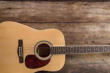Top view of guitar on dark wood floor texture in darken tone