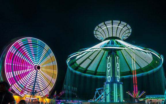 Giant Ferris Wheel and Yo-Yo amusement ride side by side in night time shot with long exposure.