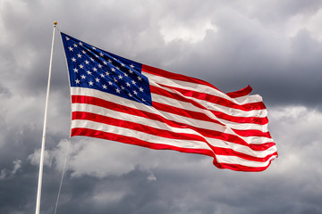 Brightly lit USA flag on a windy day against clouds
