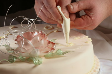 Hochzeitstorte wird vom Konditor dekoriert