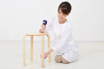 メジャーで椅子を測る女性