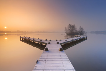 Jetty on a still lake on a foggy winter's morning