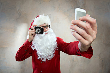 hipster santa makes selfy with retro camera and smartphone