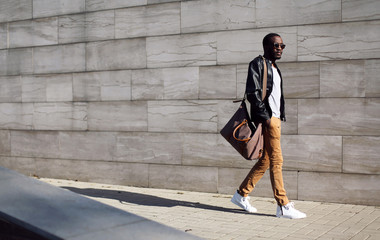 Wall Mural - Fashion stylish young african man in sunglasses and black rock l