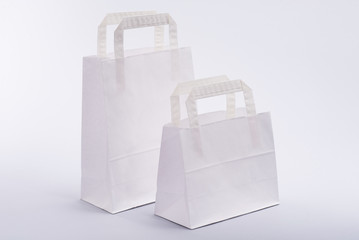 White paper shopping bag with handles on a white background
