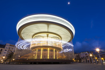 illuminated retro carousel in movement at night,