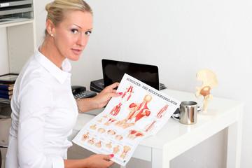 Ärztin mit Infoblatt über Schulter und Rückenmuskulatur