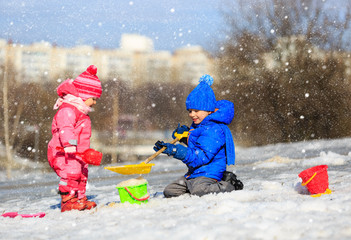 little boy and girl digging snow in winter