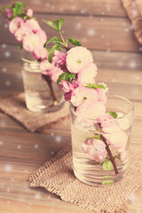 Beautiful fruit blossom in glasses on table