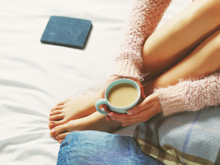 Woman relaxing at cozy home atmosphere on the bed. Young woman w