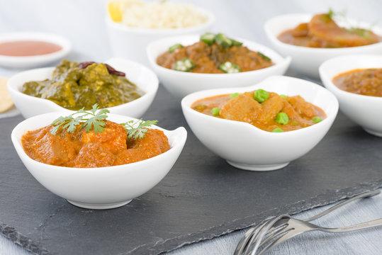 Vegetarian Curries - Selection of South Asian vegetarian curries in white bowls. Paneer Makhani, Palak Paneer, Aloo Matar, Baigan Bharta, Chilli Potatoes and Bhindi Masala, Pilau Rice and Chapattis.