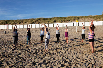 Yoga lesson in group on the beach