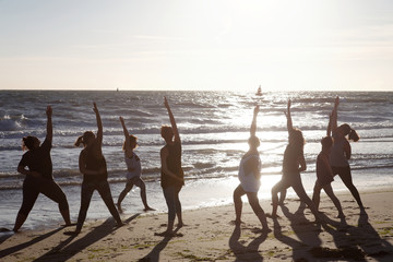 yoga exercise in group by the sea
