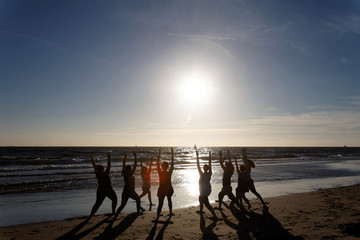 yoga in group by the sea as silhouettes