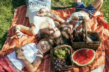 cute happy family on picnic laying on green grass mother and