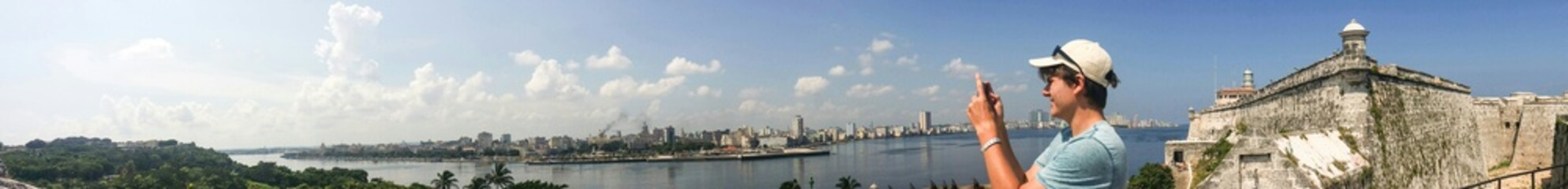Young man taking picture of Havana from Fort La Cabana