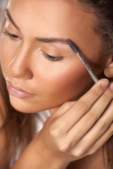 girl comb her eyebrows with a brow brush