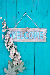Welcome sign with flowers hanging on rustic door