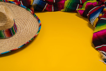 Mexican Sobrero and Serape blanket on yellow background with cop