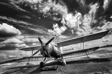 Old airplane on field in black and white