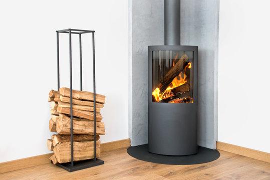 Modern burning stove next to a wood logs rack