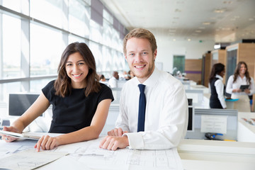Two young architects working in an office, smiling to camera
