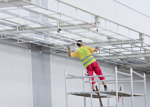 Worker painting awning on scaffolding