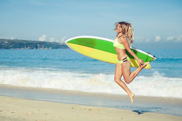 Beautiful Surfer Girl walking on the Beach