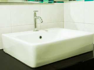 Faucet with handle and white sink