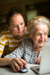 Young girl teaches elderly woman working on the computer. Granddaughter with her grandmother near the computer.