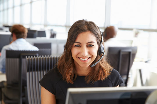 Young woman working in a call centre, looking to camera