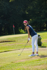 Portrait of a young woman swinging her club on a golf course.