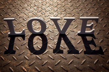 Wooden letters forming word LOVE written on metallic background
