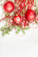 three red Xmas balls and twig on blank paper