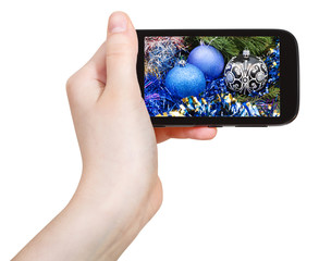 hand holds cellphone with Xmas decorations