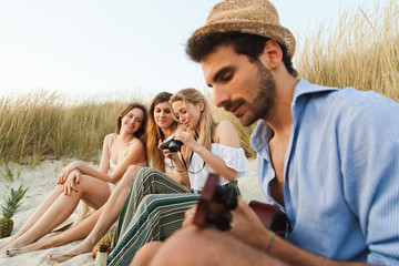 Beach at sunset. A group of young friends (a man and three women) are on the beach to relax after a day at sea, the man plays guitar while the three beautiful women taking pictures and observe