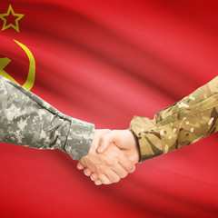 Men in uniform shaking hands with flag on background - USSR
