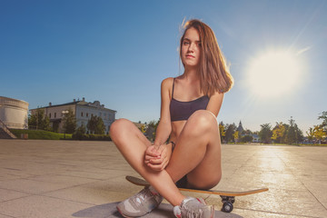 Wide angle shot of sporty women sitting on skateboard outdoors