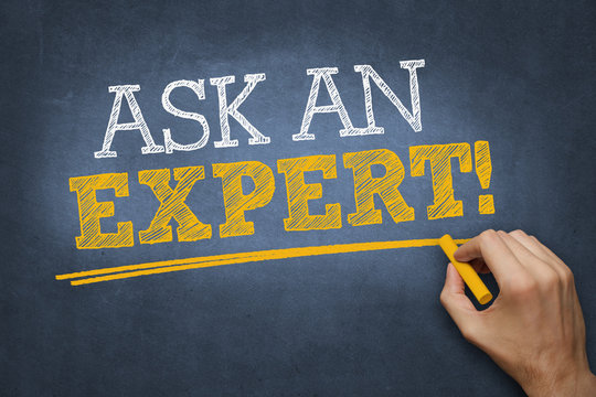 "hand writes ""ASK AN EXPERT!"" on blackboard"