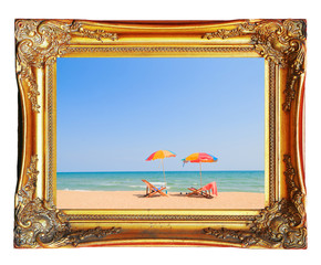 Beach chair and umbrella on sand beach in vintage picture frame