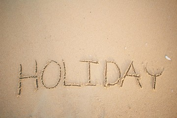 The word holiday written in sand on beach