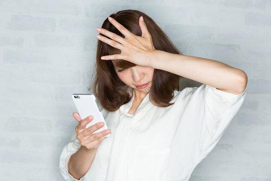 スマートフォン / 頭を抱える女性