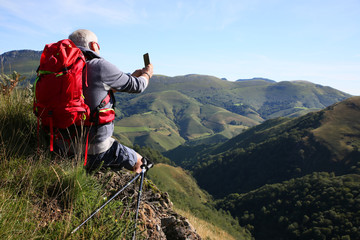 Hiker in Pyrenees mountains taking picture of scenery