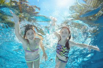 Children swim in pool or sea underwater, happy active girls have fun in water