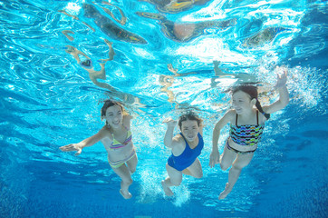 Family swim in pool or sea underwater, happy active mother and children have fun in water