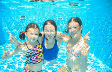 Family swim in pool underwater, happy active mother and children have fun in water