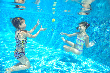 Children swim in pool underwater, happy active girls have fun in water