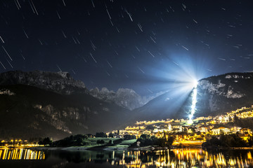 Moveno lake and city with Dolomiti of Brenta Group in background at the moonlight and star trails