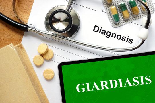 Word  Giardiasis on a book and pills.