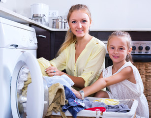 Housewife and girl doing laundry